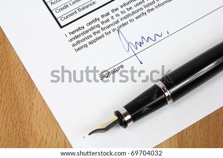 Signature under a business contract agreement with a fountain pen. The signature is fictional. - stock photo