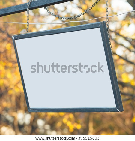 signboard with white background against the background of trees - stock photo