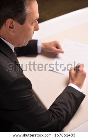 Signing a contract. Top view of mature man in formalwear signing a document - stock photo