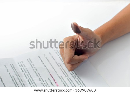 Signing a contract with a thumb print: Image contains thumb with ink stain and blurry typed paper. - stock photo