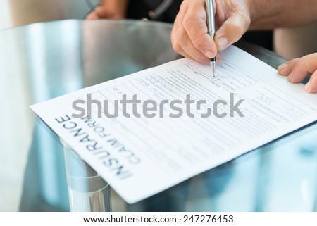 Signing insurance Claim form - stock photo
