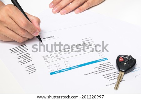 signing pen and car key for Vehicle Sales Agreement - stock photo