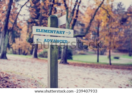 Signpost in a park or forested area with arrows pointing two opposite directions towards Elementary and Advanced. - stock photo