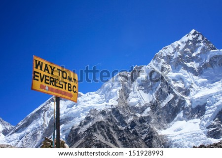 Signpost to the Mount Everest Base Camp with Nuptse mountain in the background, Nepal - stock photo