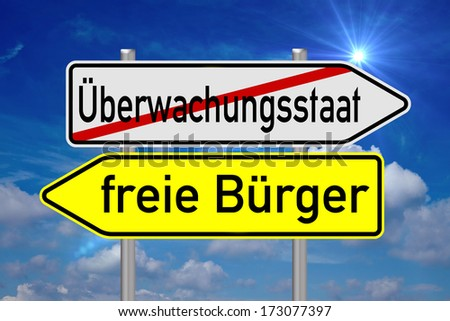 signpost with the german words surveillance state and free citizens over a blue sky with sun / surveillance state - stock photo
