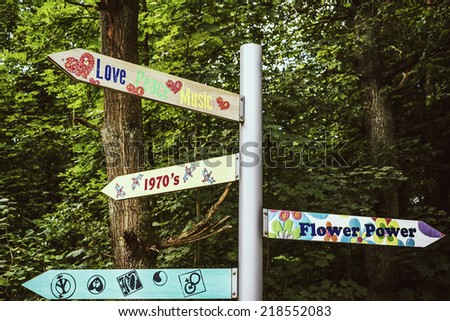signpost with vintage messages from sixties and seventies - stock photo