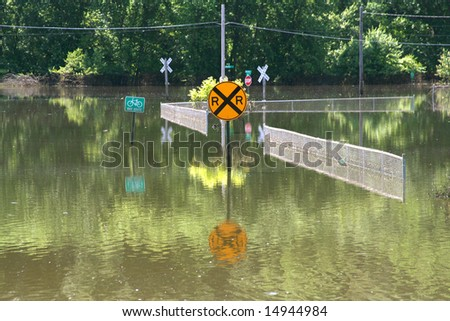 Signs and fences are submerged in flood waters. - stock photo