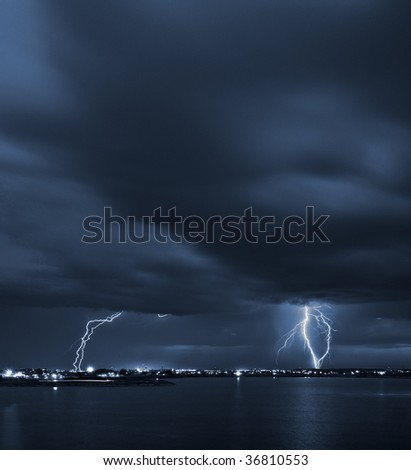 Signs - powerful lightning strikes over a lake in the city - stock photo