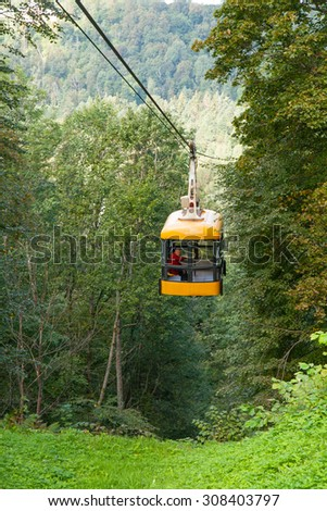 SIGULDA, LATVIA - SEPTEMBER 02, 2014 - An elderly man goes in a ropeway cabin across the river Gauja - stock photo