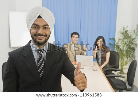 Sikh business executives showing thumbs up and smiling - stock photo
