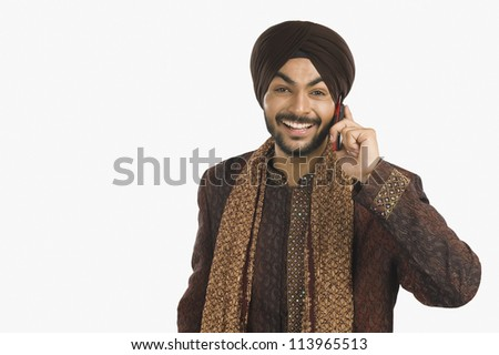 Sikh man talking on a mobile phone - stock photo