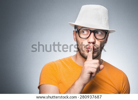 Silence. Young trendy guy with his finger on mouth - lips against gray background - stock photo