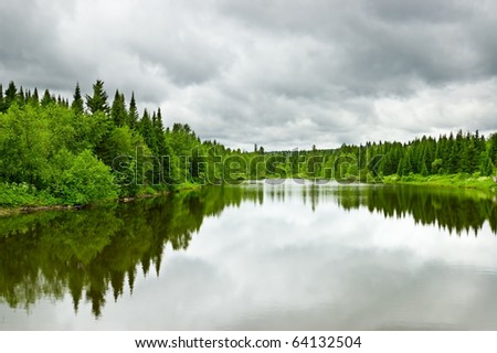 Silent lake near green forest. - stock photo