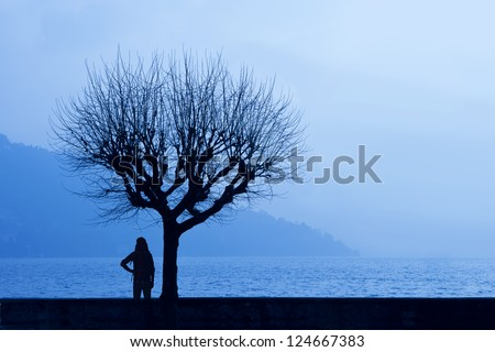 Silhoette of a hiker admiring the hazy winter dawn of a lake with misty mountains in the background underneath a tree (Lago di Como, Italy) - stock photo