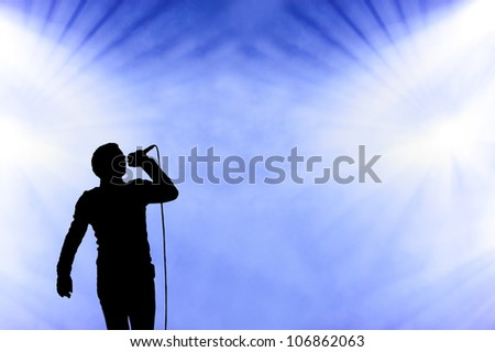 Silhoetted illistration of a male singer performing against a blue cloudy smoke filled sky at an open-air concert - stock photo