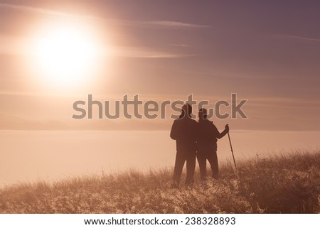 Silhouette active couple in love with Trekking pole in the morning fog. Landscape composition, background mountains and sunrise. - stock photo