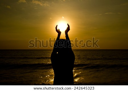 Silhouette and hand holding the sun - stock photo