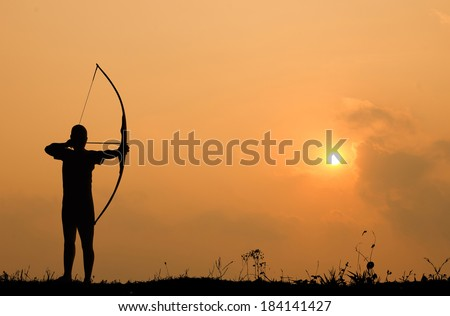 Silhouette archery shoots a bow at a target in sunset sky and cloud.  - stock photo