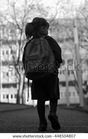 Silhouette back view of a little girl (age 6) with school bag walks to school alone by herself in the street. Education concept. vertical  copy space - stock photo