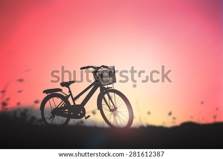 Silhouette bicycle in the meadow over beautiful sunset background. - stock photo
