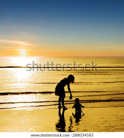 Silhouette boy mother on the beach and shadow reflect on the water. - stock photo