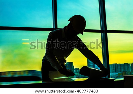 Silhouette builder engineer wear security helmet look at blueprint paper construction drawing plan on background of sunset window frame blue yellow sky with clouds - stock photo
