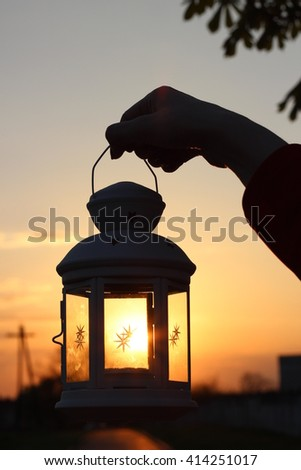 Silhouette candle lantern lamp in the hand of the girl in the rays of the setting sun - stock photo