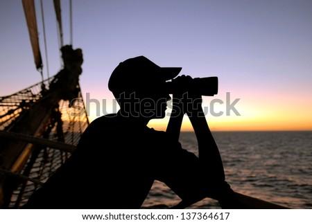 silhouette captain looking through binoculars - stock photo