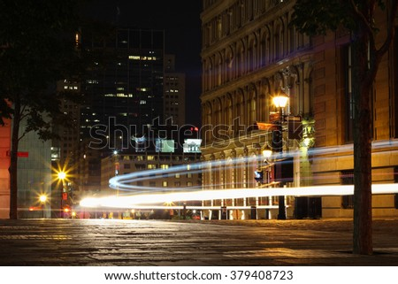 Silhouette cars with red rear light and traffic lights, with Chinatown in the background, in Old Montreal at dark night  - stock photo