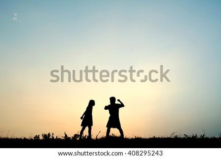 Silhouette children quarrel at sky sunset - stock photo