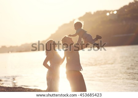 Silhouette concept. Happy mother and father playing with little son at sunset. Young caucasian mom and dad with her baby boy having fun outdoor in evening. Happy family - stock photo