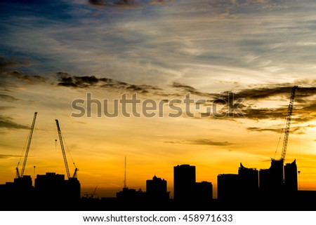 Silhouette construction during sunrise and orange sky.  - stock photo