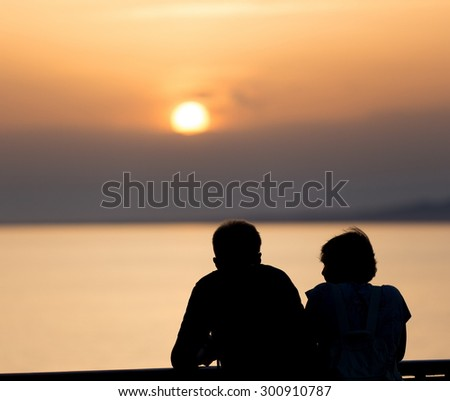 silhouette couple looking sunset on the balcony - stock photo