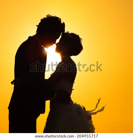 Silhouette couple love with sunset - stock photo