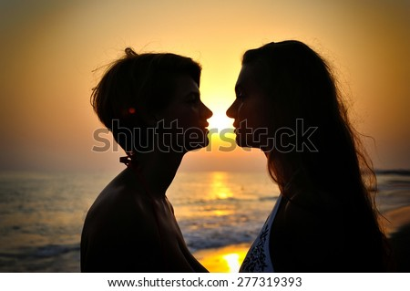 Silhouette couple over sunset background - stock photo
