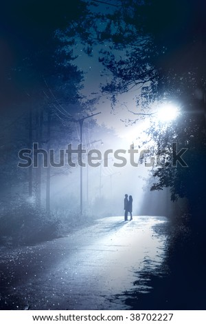 silhouette couple stand together in the moonlight - stock photo