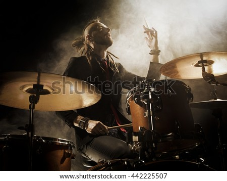 Silhouette drummer on stage. Dark background, smoke spotlights - stock photo