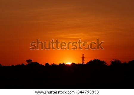 Silhouette electric tower and the sun in evening time.Sunset style. - stock photo