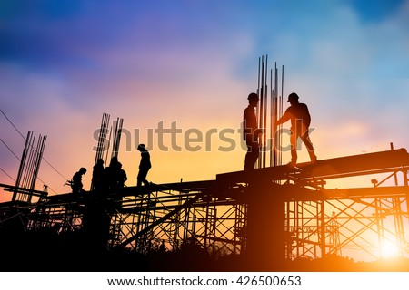 Silhouette engineer standing orders for construction crews to work safely on high ground over blurred natural background sunset pastel. heavy industry and safety at work concept. - stock photo