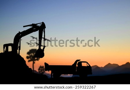 silhouette Excavator and truck working at construction site - stock photo