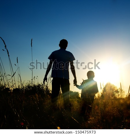 Silhouette father and son at sunset  - stock photo