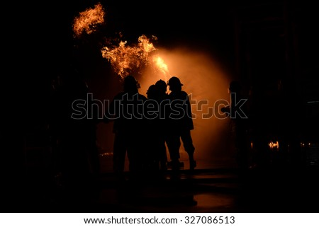 silhouette fire fighter at night. - stock photo
