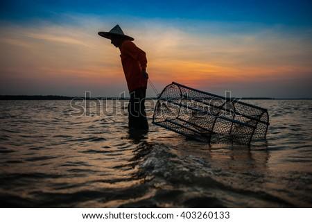 Silhouette fisherman evening lamps, of fishing gear.   - stock photo