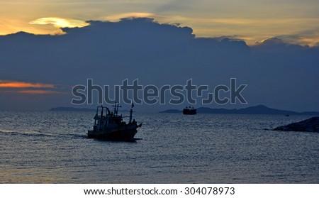 Silhouette fishing boats returning home during sunset, near Pattya beach - stock photo
