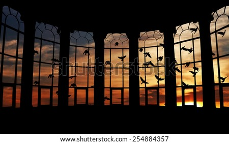 Silhouette flocks of birds flying in a surreal candy-color sunset sky outside a bay window frame. - stock photo