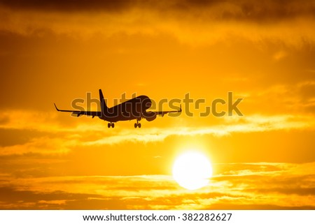 Silhouette from a landing plane that is flying to the airport. Photo taken during a nice colorful sunrise. - stock photo
