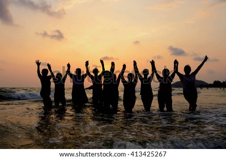 Silhouette Group of People have fun on beach - stock photo