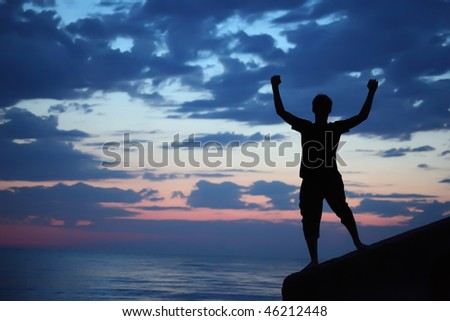 Silhouette guy lifted hands upwards on breakwater in evening near sea - stock photo