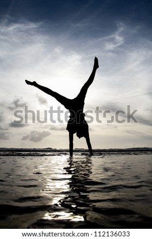 silhouette gymnast in water - stock photo