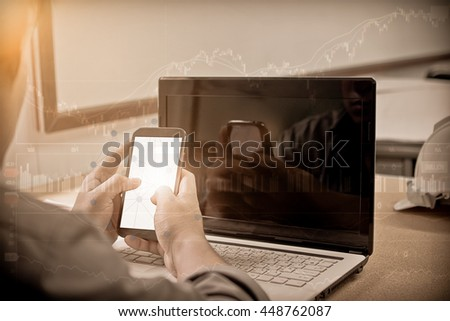Silhouette hand business man working with smartphone and computer to work wireless. Press OK Trading on computer. Concept boundless business and technology flare light.selected focus.sepia tone - stock photo